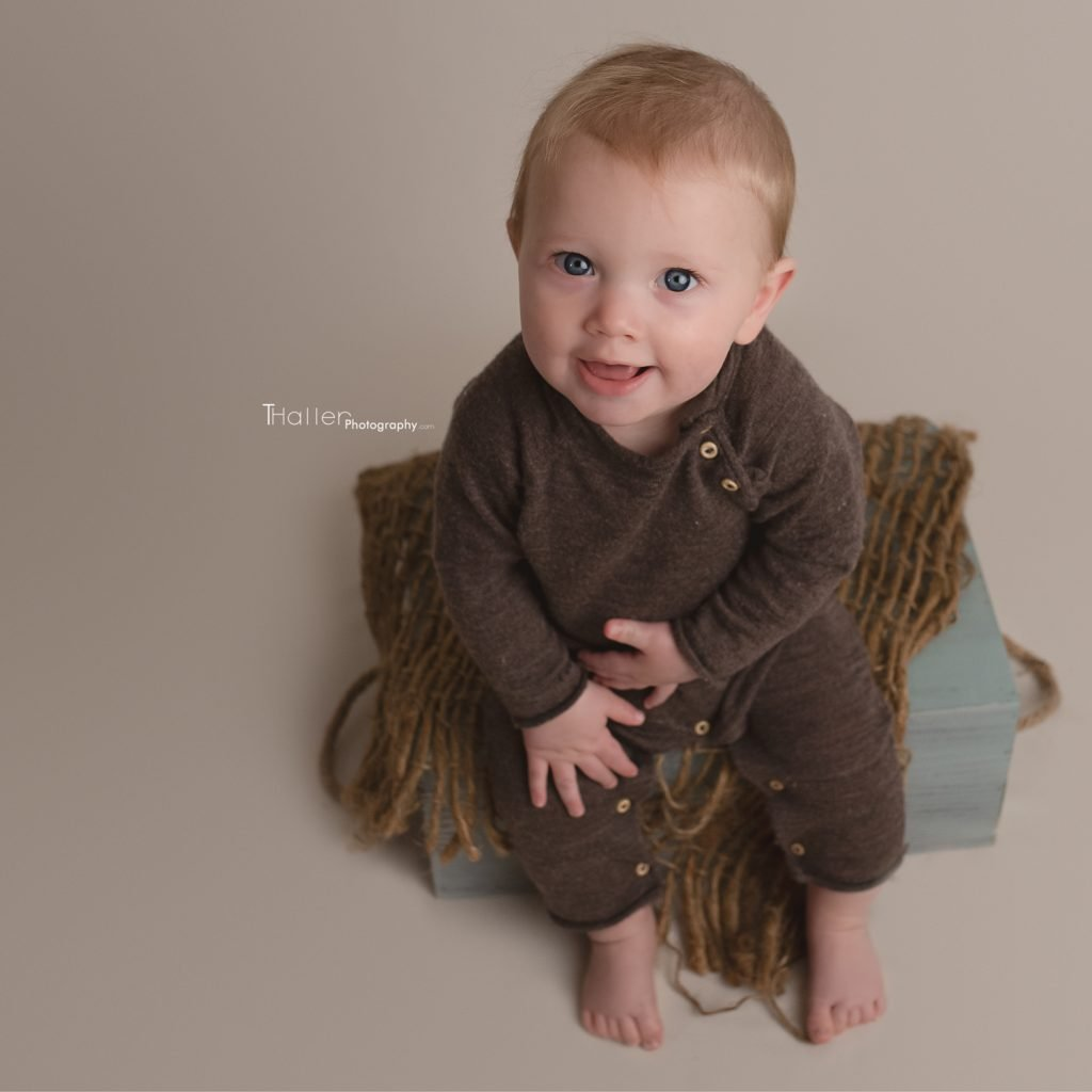 North Vancouver Newborn, Baby & Maternity Photographer Photo of a baby sitting and smiling on a box from birds eye view
