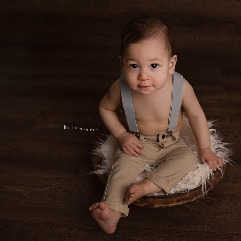 North Vancouver Newborn, Baby & Maternity Photographer Baby boy looking at the camera sitting in a brown wooden bowl