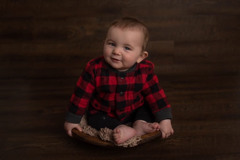 North Vancouver Baby Photography studio - Baby boy wearing a red and black plaid shirt sitting in a wooden bowl and smiling