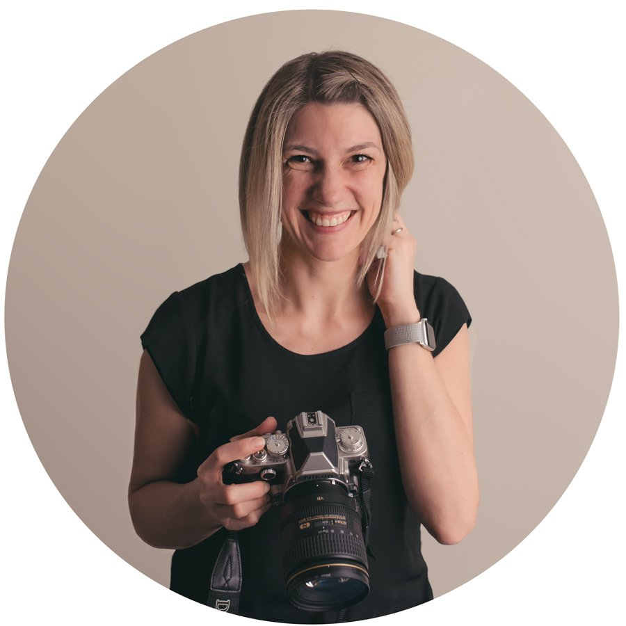 Photographer holding a camera and smiling