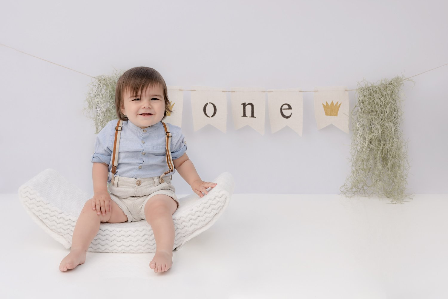 North Vancouver Photography Studio - Cake Smash - First Birthday Portrait picture of a 1 year old sitting in front of a banner with the word one