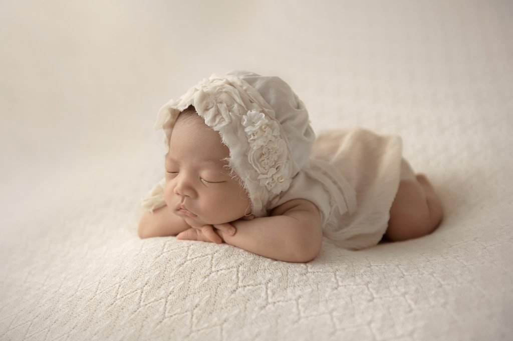 Newborn Photo Shoot Vancouver - Side view of a baby girl sleeping on her tummy resting her head on her hands