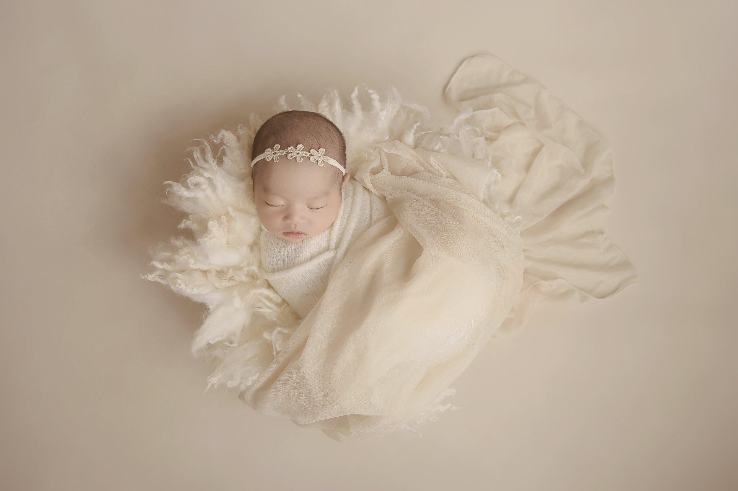 newborn girl sleeping wearing a flower headband