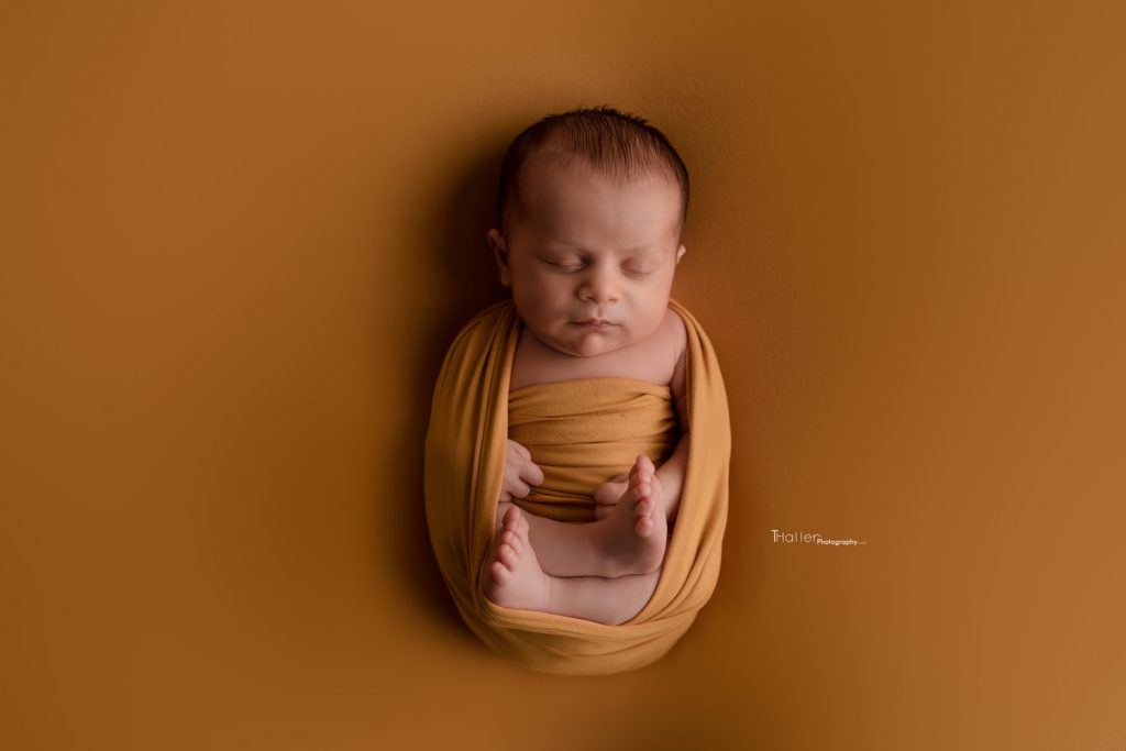 Burnaby Newborn Photographer baby sleeping wrapped in a mustard wrap with feet showing