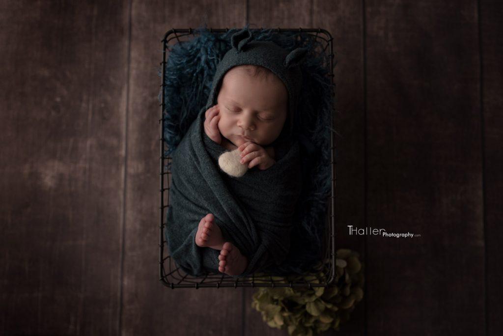 Sleeping newborn in a basket holding a heart wearing a hat
