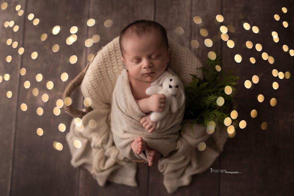 Newborn baby boy sleeping in a basket holding a little teddy bear