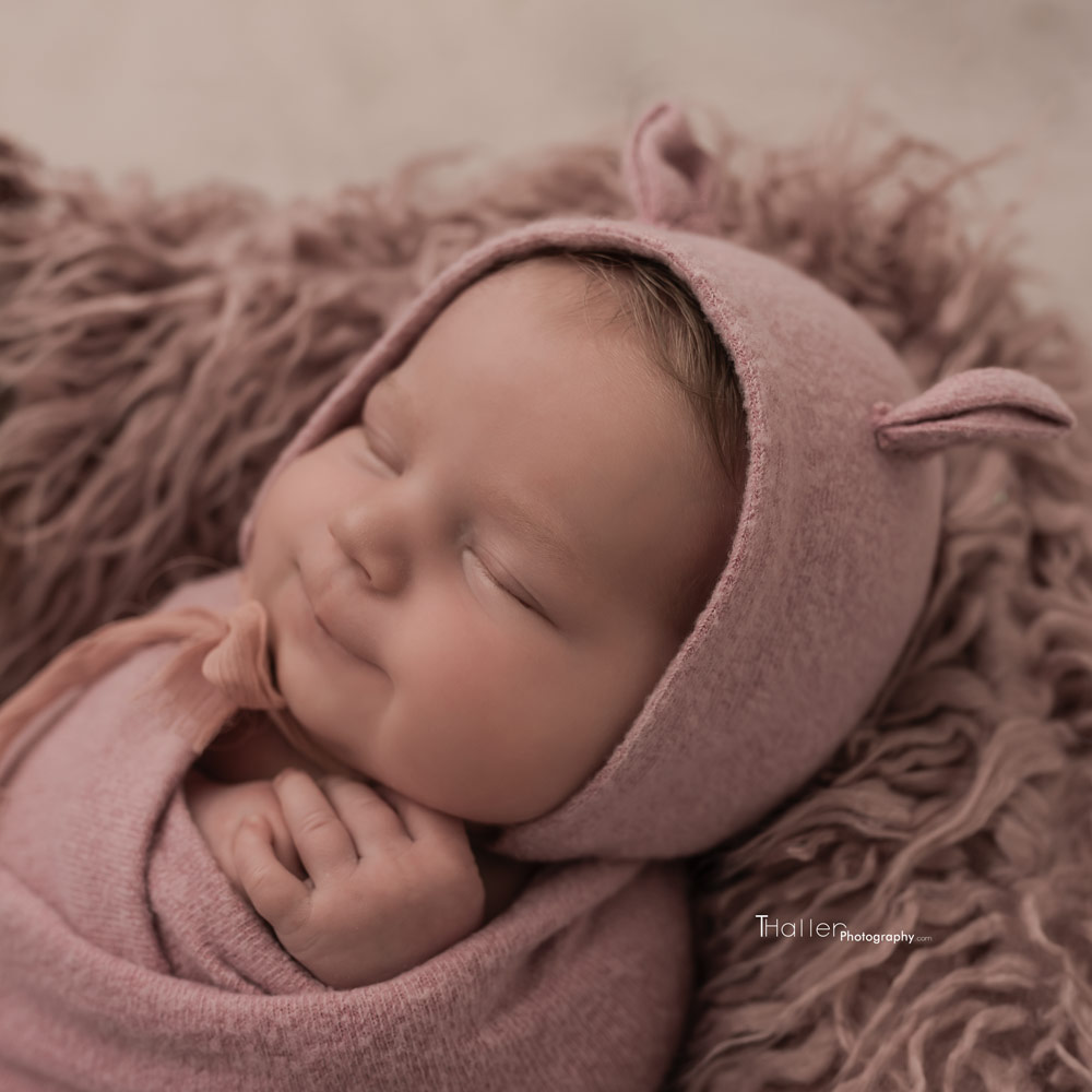 newborn baby girl sleeping and smiling wearing a pink hat with little ears