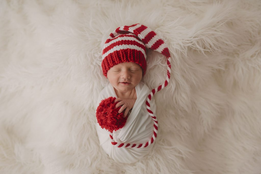 Newborn baby smiling in his sleep wearing a Christmas hat