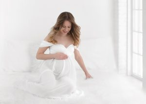 North Vancouver Maternity Photographer - Pregnant woman sitting on a bed