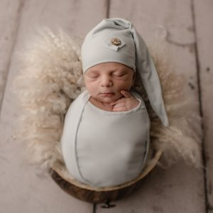 Newborn Baby Boy posed in a bucket with a light blue sleepy hat - shot taken by a professional newborn photographer