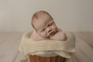 Baby Boy sleeping on his arms posed in a bucket - Best Newborn Photographer Vancouver