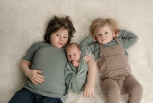 Portrait of two boys and their newborn baby brother