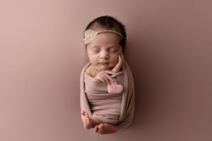 Baby girl holding a pink heart sleeping on a rose coloured backdrop