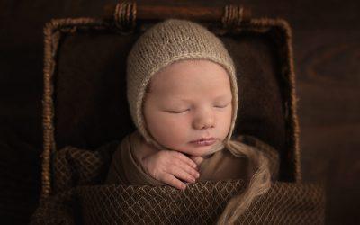 Newborn Photographer North Vancouver - Newborn boy wearing a bonnet sleeping in a basket